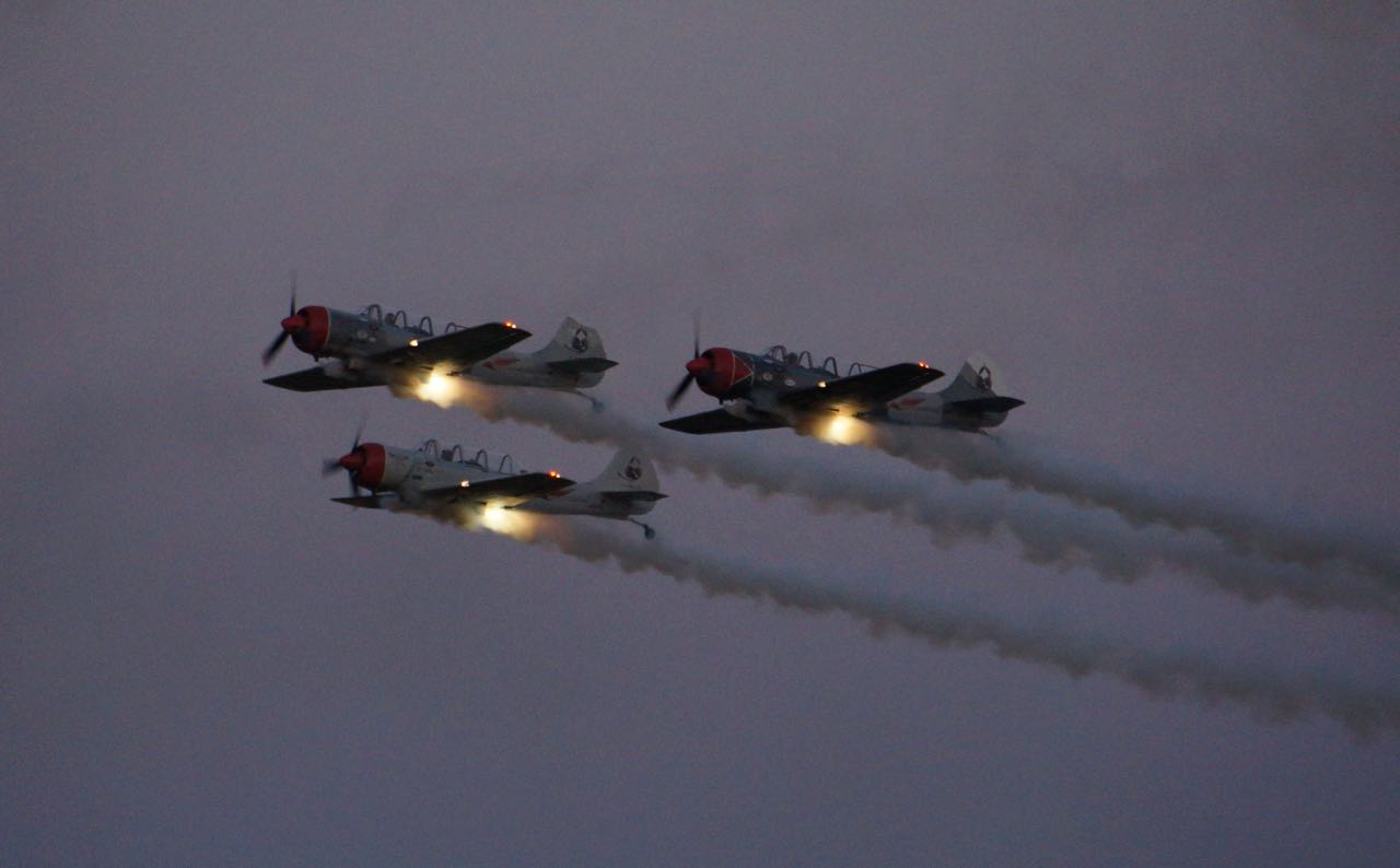 Three planes flying in formation through the night with bright light sources on the wings.